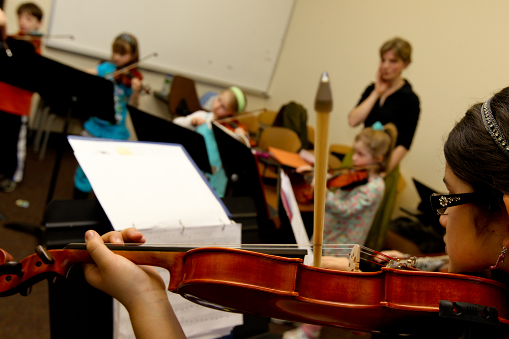 children practicing violin in class